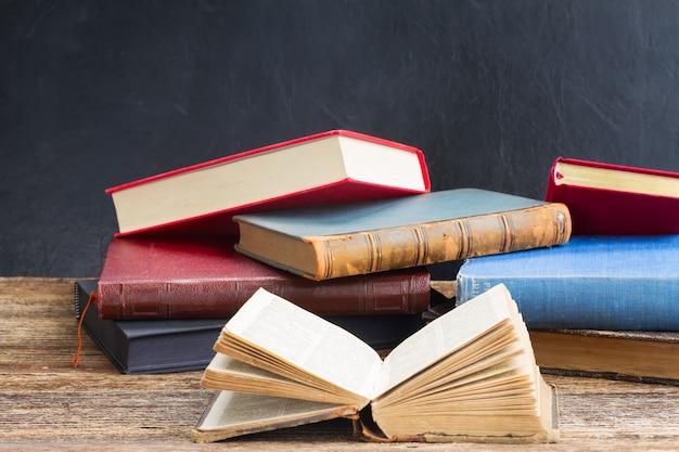Ouvrir le vieux livre avec pile de fermé sur une étagère en bois
