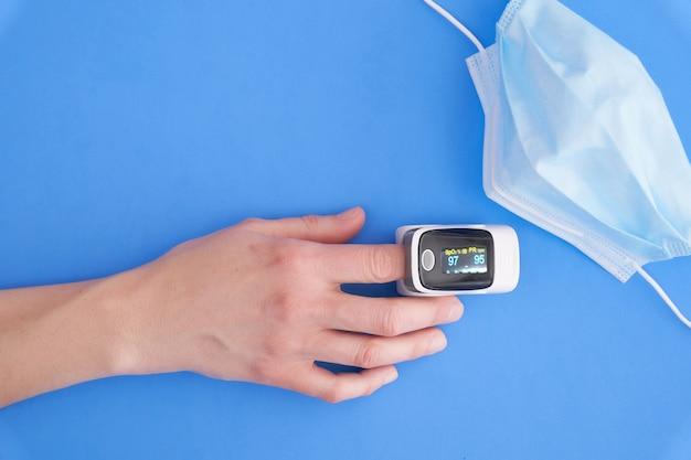 Oxymètre sur le doigt sur fond bleu