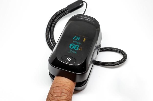 Oxymètre noir pour mesurer la saturation en oxygène du sang sur fond blanc.
