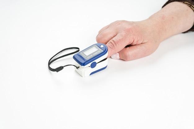 Oxymètre de pouls digital portable sur une main de femme isolée sur blanc