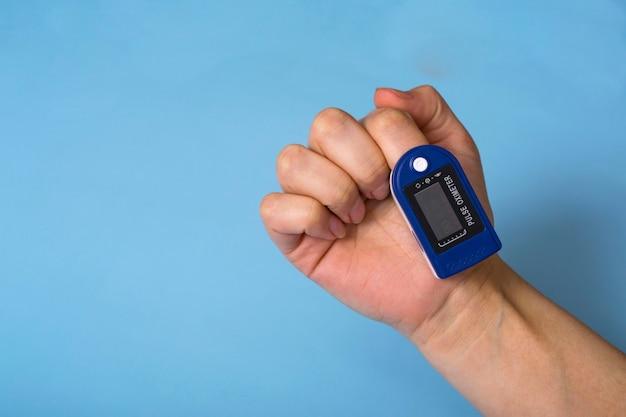 Un oxymètre de pouls est sur la main de la femme. un oxymètre de pouls utilisé pour mesurer la fréquence cardiaque et les niveaux d'oxygène. covid-19