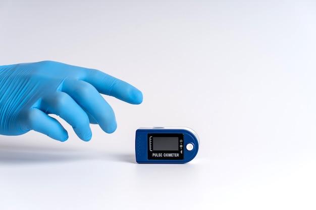 Oxymètre de pouls sur fond blanc. une main dans un gant médical tient un appareil de diagnostic de la santé.