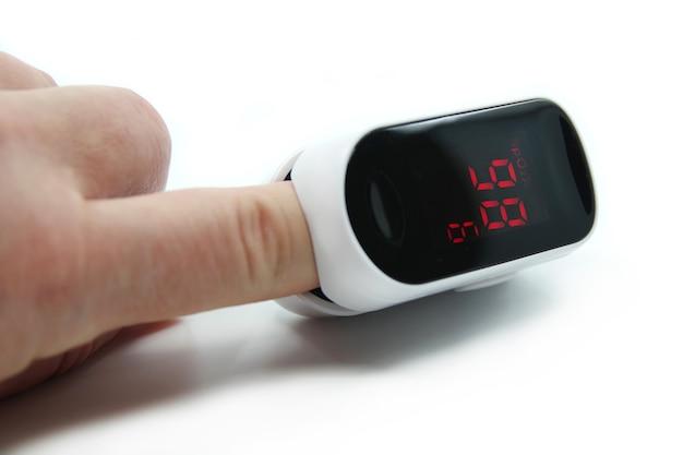 Oxymètre de pouls isolé sur une surface blanche. oxymètre de pouls utilisé pour mesurer la fréquence du pouls et les niveaux d'oxygène. gros plan du doigt dans un oxymètre.