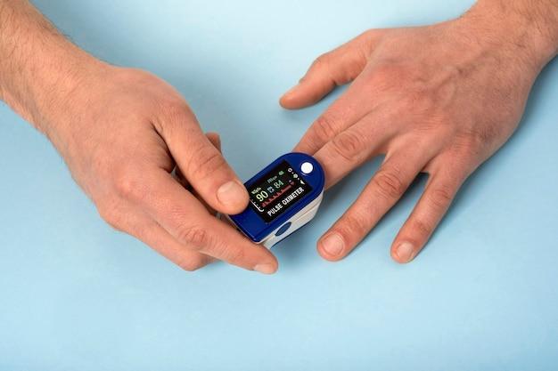 Oxymètre de pouls de la main humaine utilisé pour mesurer la fréquence du pouls et les niveaux d'oxygène avec un fond bleu médical avec espace de copie.