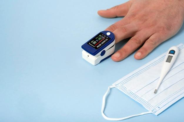 Oxymètre de pouls des mains de l'homme humain utilisé pour mesurer la fréquence du pouls et les niveaux d'oxygène avec un fond bleu médical avec espace de copie.