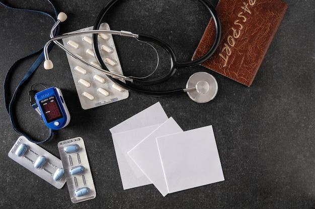 Oxymètre de pouls, oxymètre sanguin, thermomètre électronique, passeport, tonomètre, pilules sur une surface grise