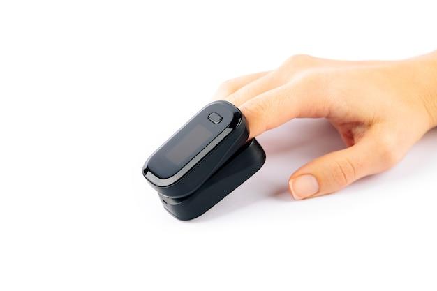 Oxymètre de pouls utilisé pour mesurer la fréquence du pouls et les niveaux d'oxygène à portée de main isolé sur fond blanc