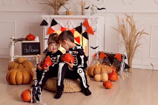 Oy et fille en costume de squelette halloween avec citrouille