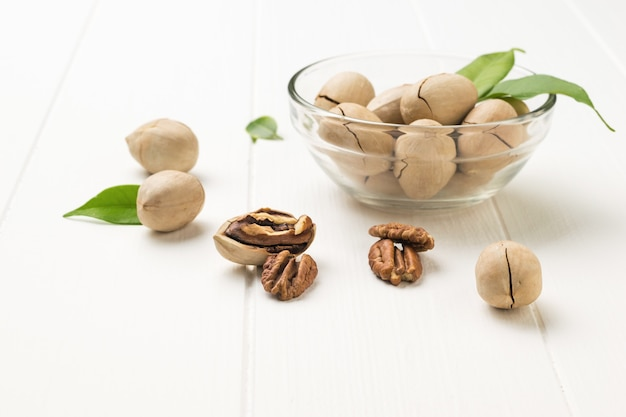 Pacanes dans un bol avec des feuilles sur une table en bois. la nourriture végétarienne.