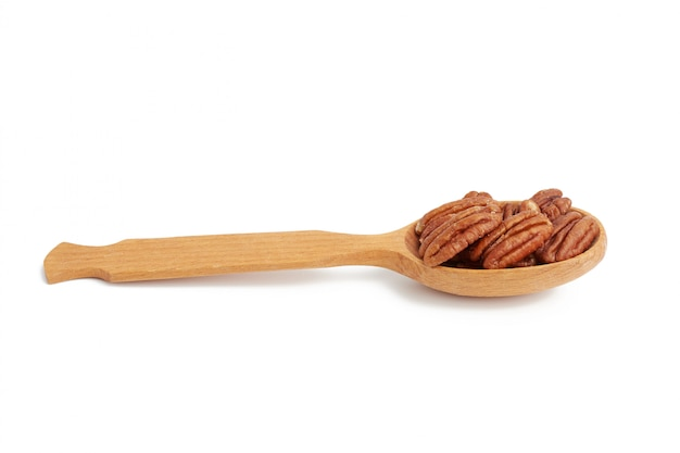 Pacanes pelées dans une cuillère en bois brun isolé sur fond blanc, gros plan
