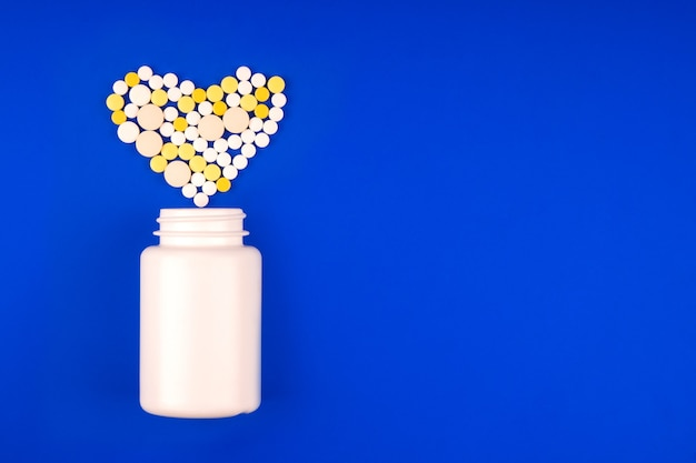 Pack avec un tas de pilules multicolores médicales sous la forme d'un cœur sur fond bleu