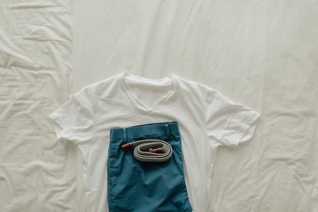 Pack de vêtements sur lit blanc avec un t-shirt blanc bleu court et vêtir la ceinture.
