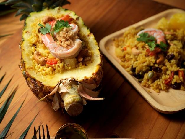 Pad de riz kao à l'ananas sapparod dans une assiette et bol d'ananas coupé