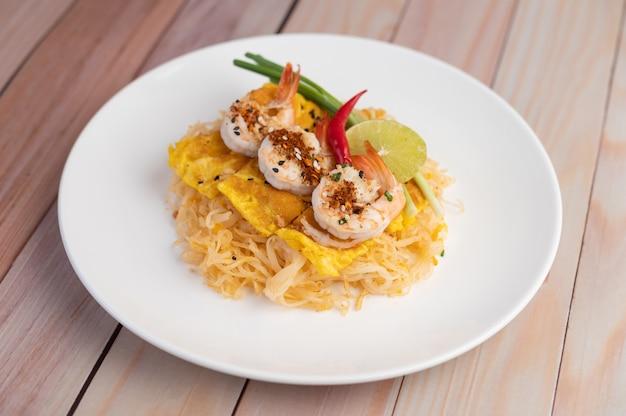 Pad thai crevettes fraîches dans une assiette blanche.