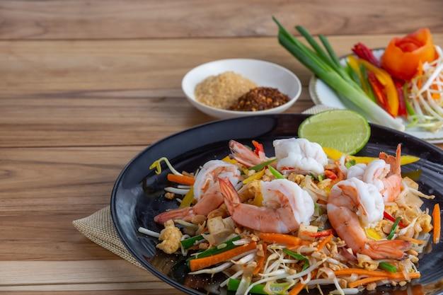 Pad thai, crevettes fraîches dans un plat noir, posées sur une table en bois.