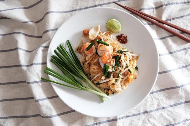 Pad thai, crevettes roses, calmar, avec du piment, citron vert et légumes sur le côté