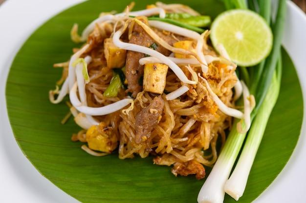 Pad thai dans une assiette blanche au citron sur une table en bois