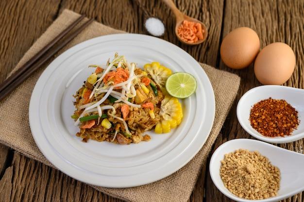 Pad thai dans une assiette blanche avec du citron, des œufs et des assaisonnements sur une table en bois.