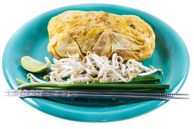 Pad thai, nouilles sautées de cuisine thaïlandaise aux crevettes.envelopper les œufs sur une plaque blanche