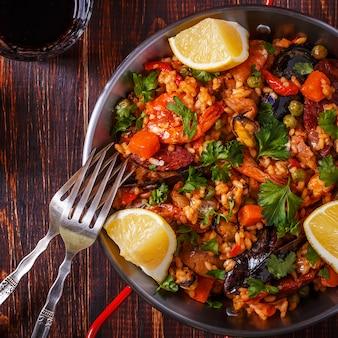 Paella au poulet, chorizo, fruits de mer, légumes et safran servis dans la poêle traditionnelle.