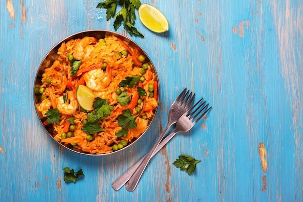 Paella espagnole traditionnelle avec fruits de mer, pois, riz et poulet