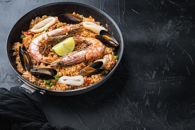 Paella valenciana avec gambas, moules et calamars sur fond noir