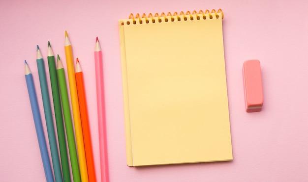 Page blanche de tampon de croquis en spirale verticale avec des crayons de couleur rose