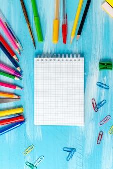 Page de bloc-notes vierge avec stylos, crayons, pinceaux, feutres, marqueurs, trombones