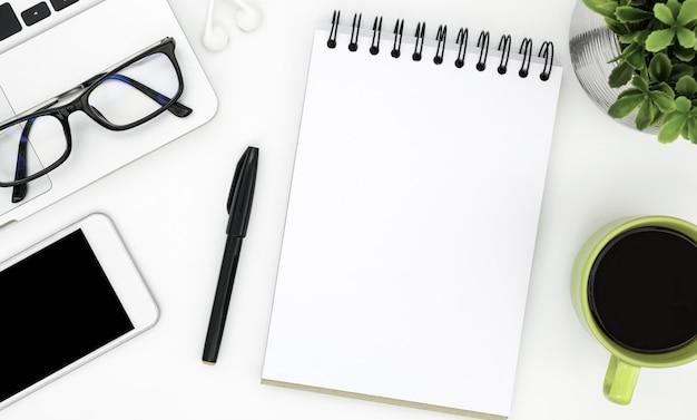 Page de cahier vierge au milieu de la table de bureau blanc.
