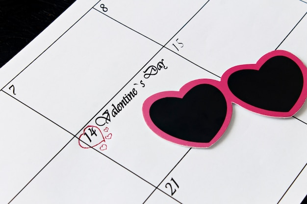 Page de calendrier avec coeurs le 14 février, jour de la saint-valentin sur fond noir.