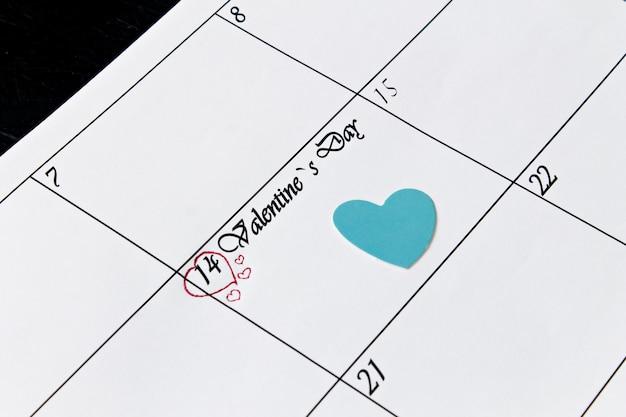 Page de calendrier avec des coeurs bleus le 14 février, jour de la saint-valentin sur fond noir.