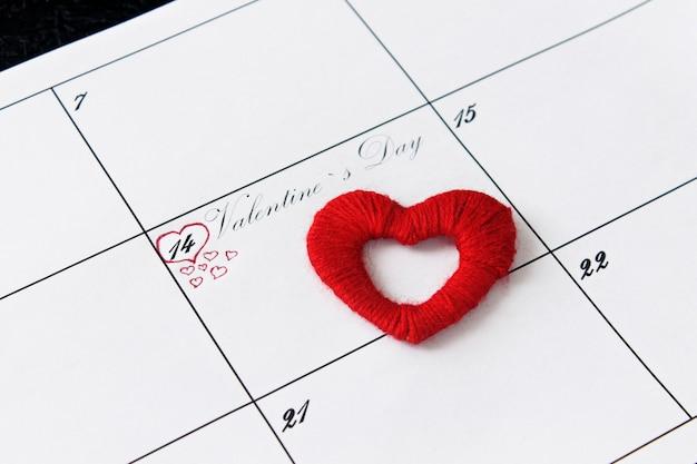 Page de calendrier avec des coeurs rouges le 14 février, saint valentin sur fond noir.