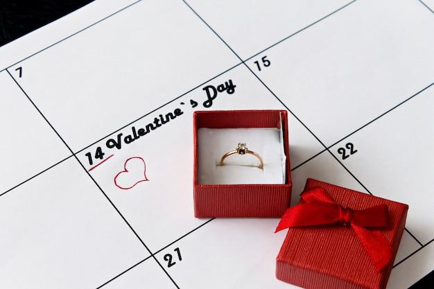 Page de calendrier avec des coeurs rouges et un cadeau le 14 février, jour de la saint-valentin o