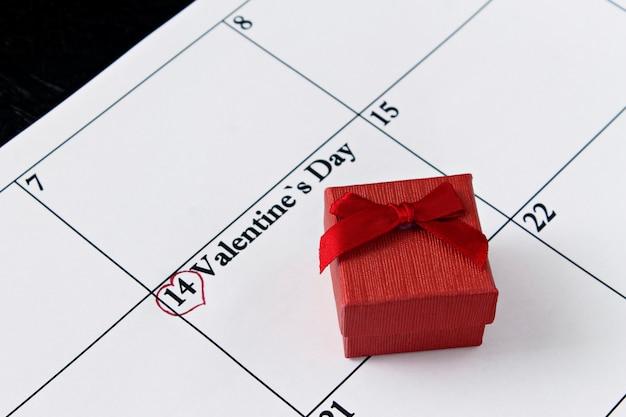 Page de calendrier avec des coeurs rouges et un cadeau le 14 février, jour de la saint-valentin