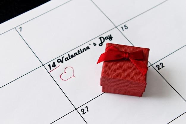 Page de calendrier avec des coeurs rouges et un cadeau le 14 février