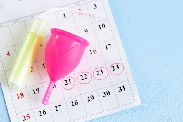 Page de calendrier et coupe menstruelle se bouchent sur la table