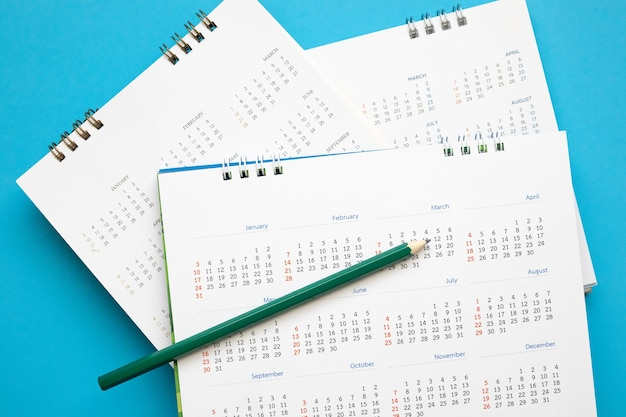 Page de calendrier avec un crayon gros plan sur le concept de réunion de rendez-vous de planification d'entreprise de mur bleu
