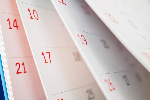 Page de calendrier feuille de retournement gros plan sur le fond de la table de bureau plan d'affaires planification de rendez-vous réunion concept