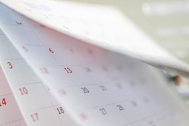 Page de calendrier feuille de retournement gros plan sur la table de bureau fond intérieur plan d'affaires planification rendez-vous réunion concept