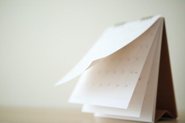 Page de calendrier flou feuille de retournement sur table en bois