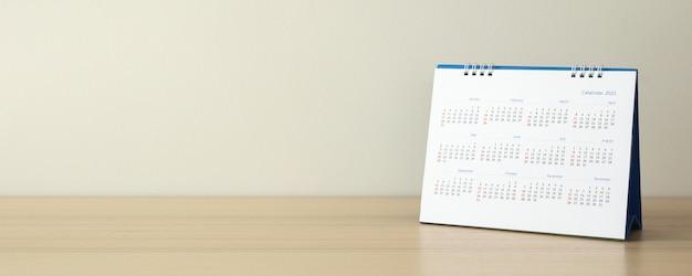 Page de calendrier gros plan sur table en bois avec fond de mur blanc concept de réunion de planification d'entreprise