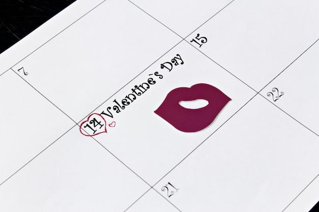 Page de calendrier avec les lèvres le 14 février, jour de la saint-valentin sur fond noir.