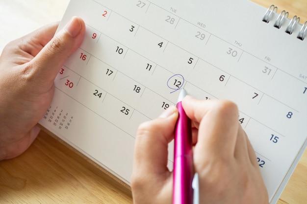 Page de calendrier avec une main féminine tenant un stylo sur la table de bureau