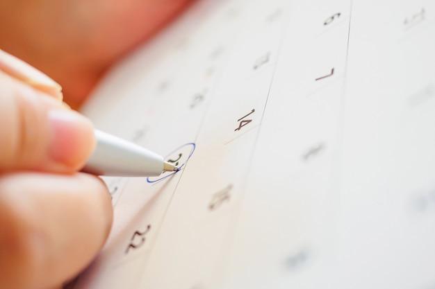 Page de calendrier avec une main féminine tenant un stylo