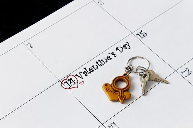 Page de calendrier avec porte-clés le 14 février, jour de la saint-valentin sur fond noir.