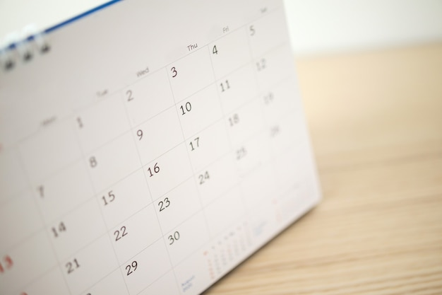 Page de calendrier se bouchent sur une table en bois avec un fond de mur blanc
