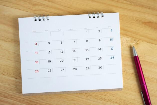 Page de calendrier avec stylo sur table de bureau en bois