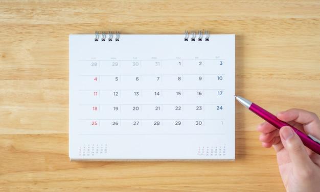 Page de calendrier sur table avec main féminine tenant un stylo, vue de dessus