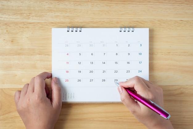Page de calendrier sur table avec stylo à main féminine