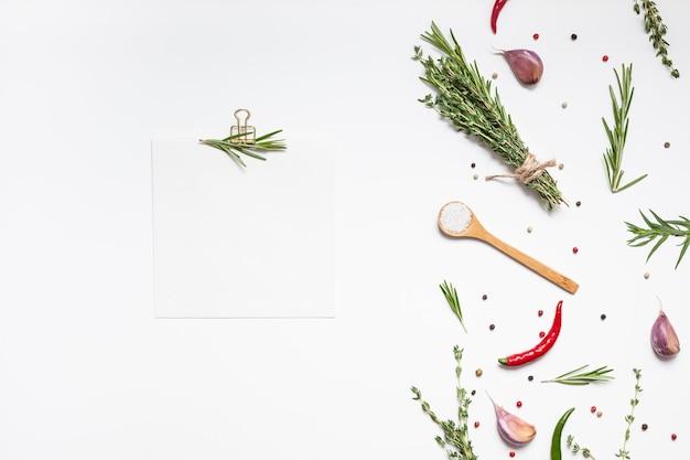 Page de papier de recette vierge avec vue aérienne à plat avec carte d'invitation à l'espace de texte de maquette de clip sur fond blanc avec des herbes vertes et des épices. conception de blog de cuisine de livre de recettes de menu avec des ingrédients de cuisine